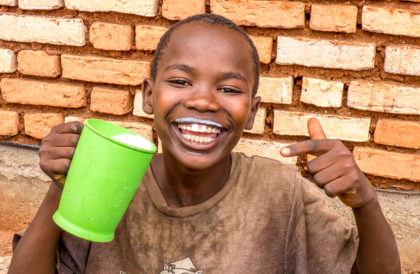 Burundian boy drinking milk