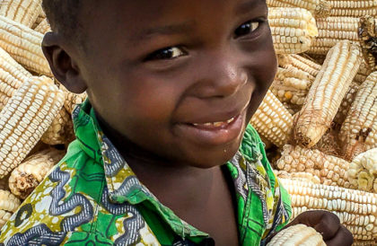 Little Burundian boy with Foundations For Farming maize harvest